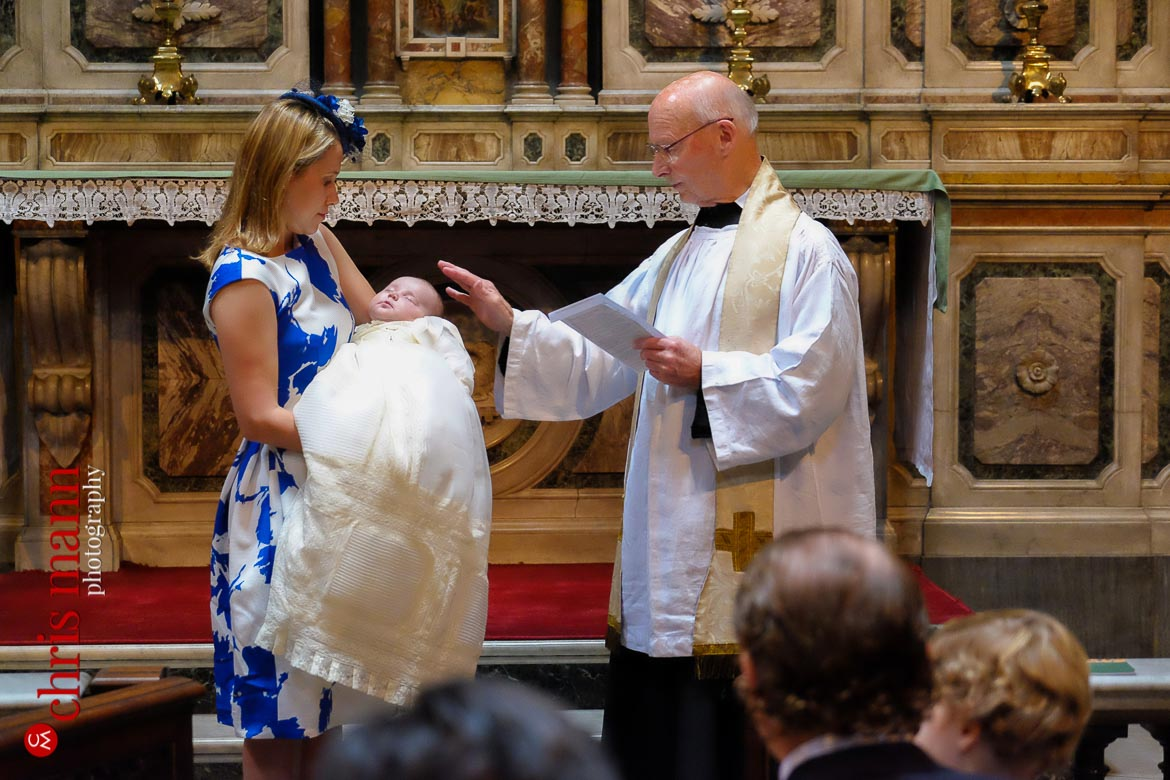 Catholic priest blesses baby after christening ceremony Brompton Oratory Knightsbridge London