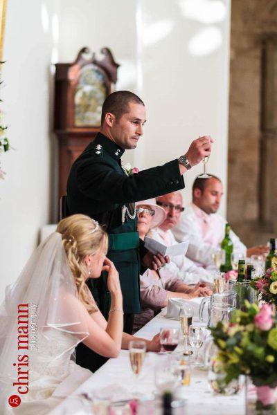 groom raises glass in toast wedding reception Farnham Castle Great Hall