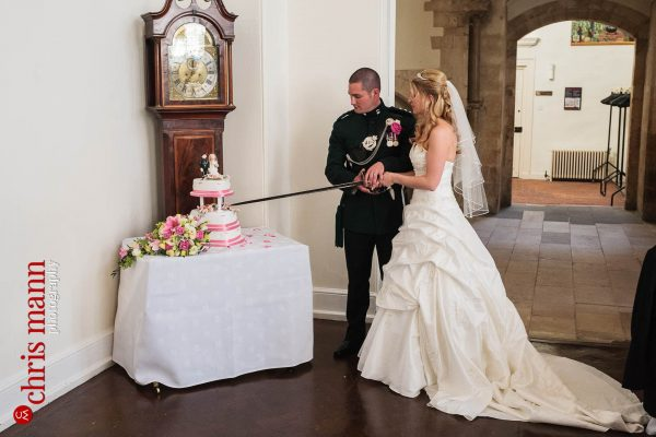 bride and groom cut wedding cake with sword wedding reception Farnham Castle Great Hall