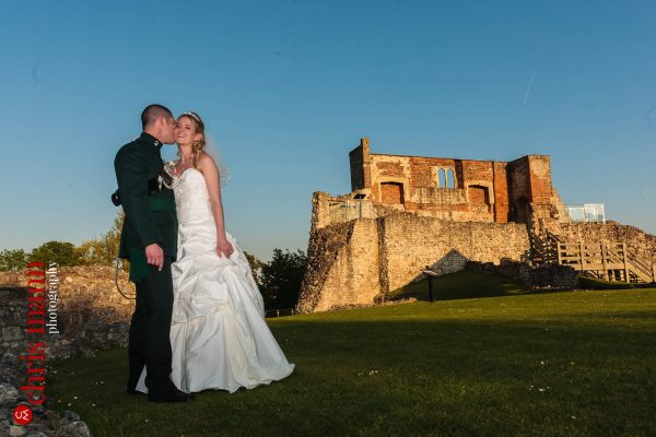 bride and groom kiss on lawn at the Keep Farnham Castle Surrey