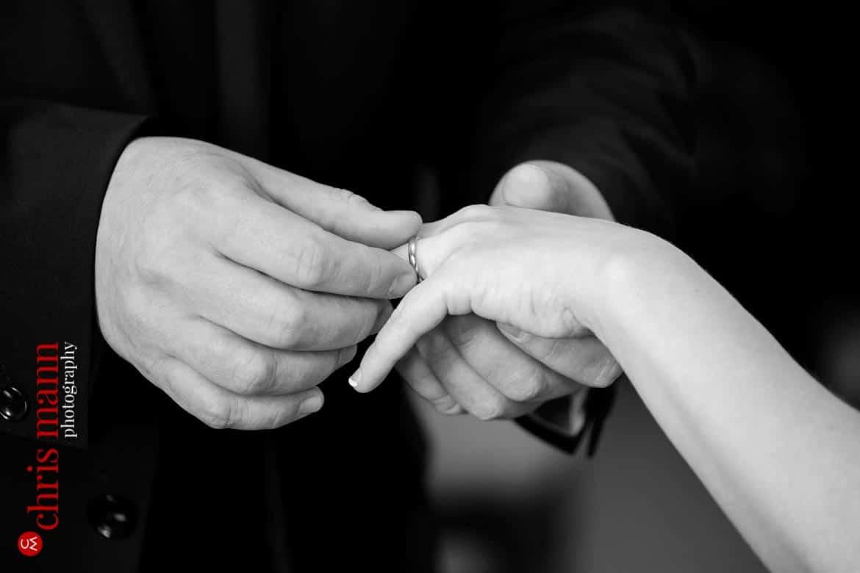 groom puts ring on bride's finger Artington House Guildford register office