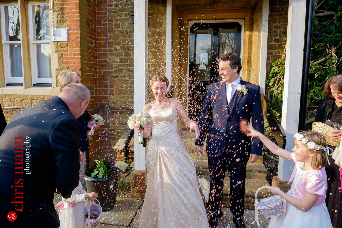 bride and groom showered with confetti Artington House Guildford register office