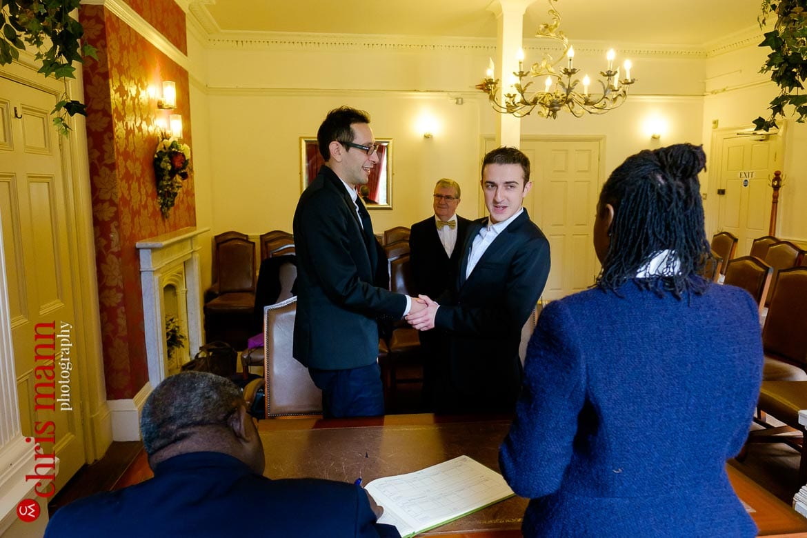 two grooms hold hands Southwark Register Office civil ceremony
