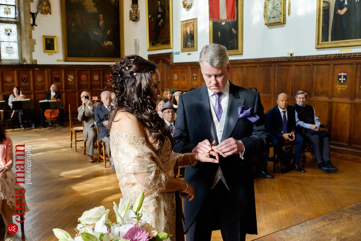 groom places ring on bride's finger Museum of the Order of St. John Wedding London