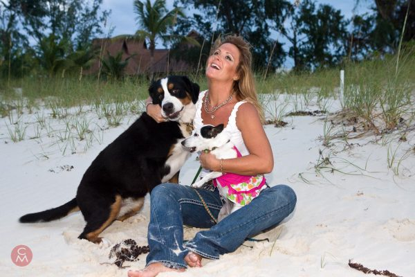 happy woman sitting on beach with two dogs portrait photography Chris Mann