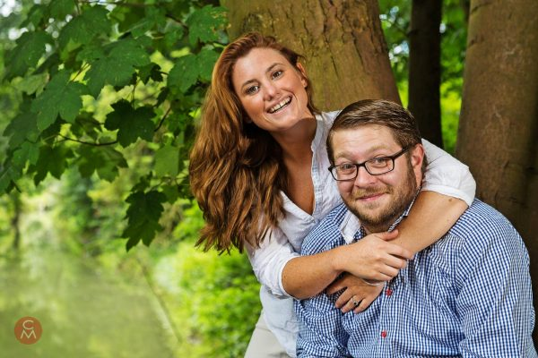happy couple with dog sitting by tree portrait photography Chris Mann