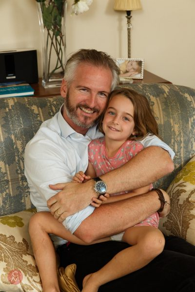 father embraces daughter interior portrait photography Chris Mann