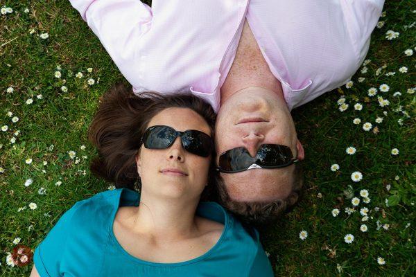 couple head to head lying on grass sunglasses portrait photography Chris Mann