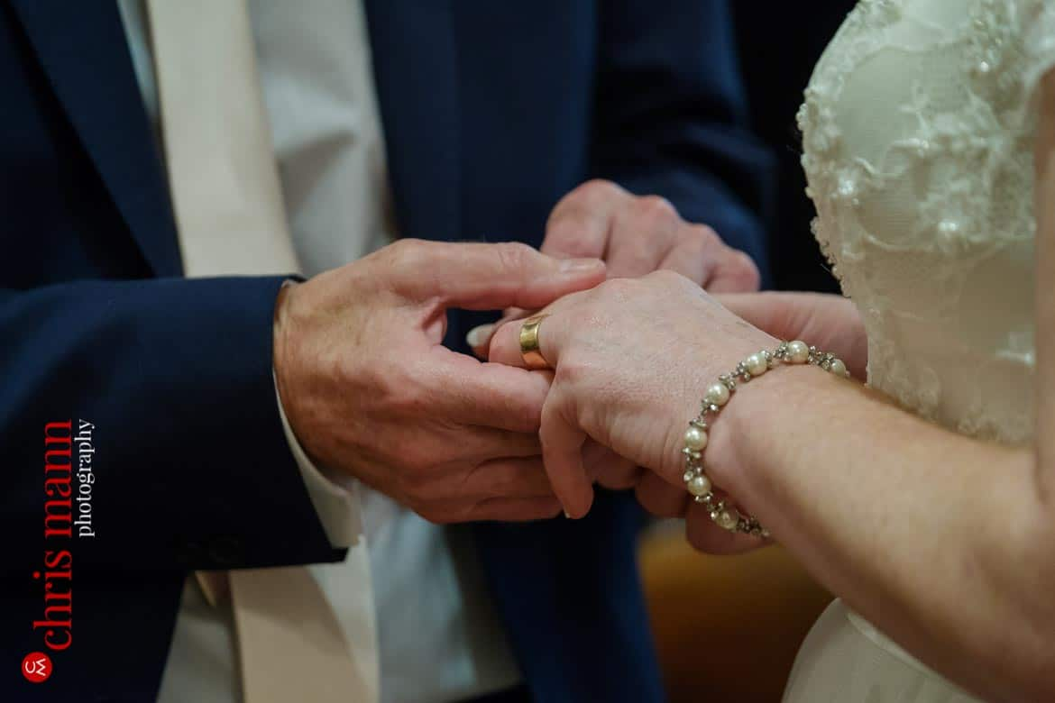 groom puts ring on bride's finger at Oxford Register Office Wedding