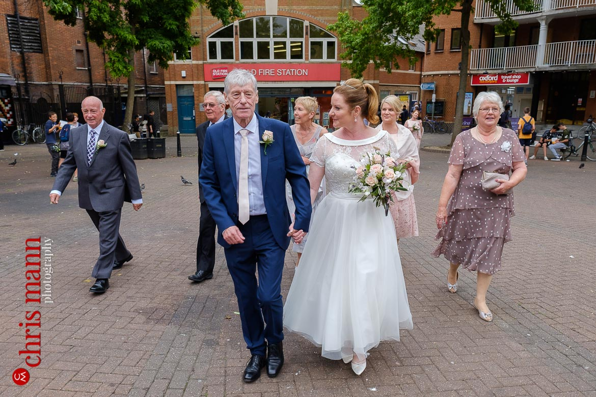 bride and groom and wedding party walk through Gloucester Green Square after Oxford Register Office Wedding