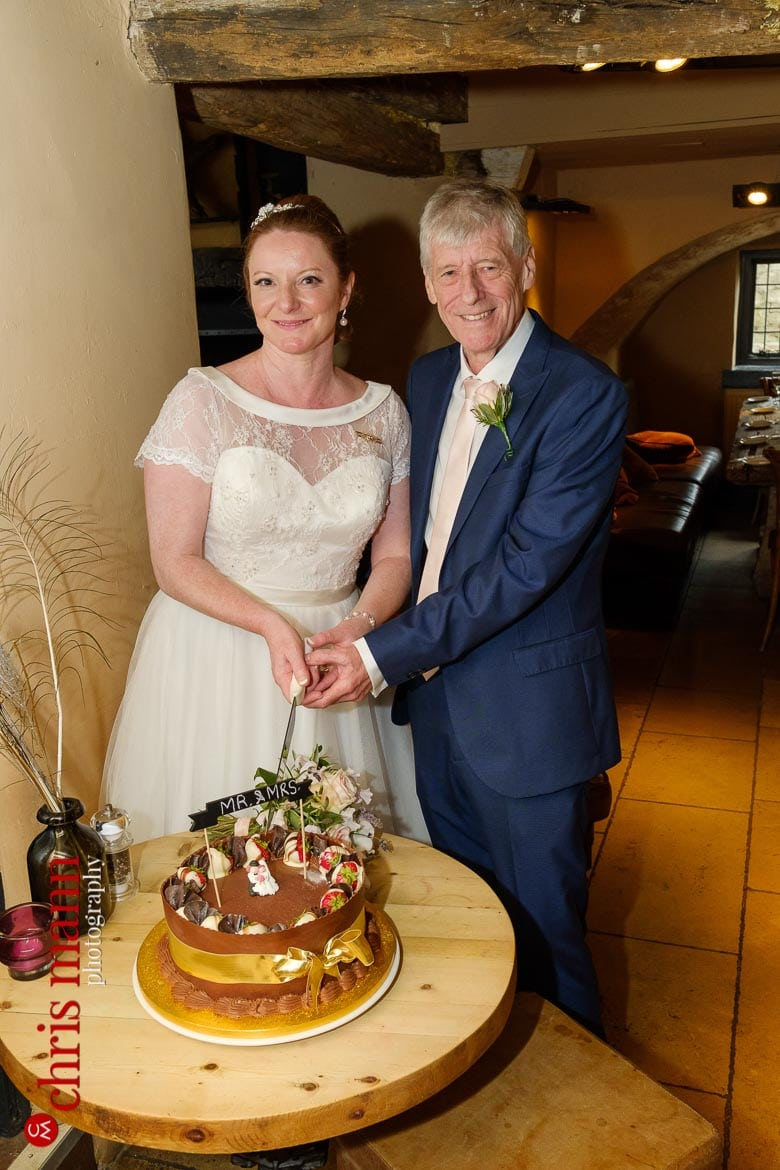 bride and groom cut cake at Trout Inn Wolvercote Oxford