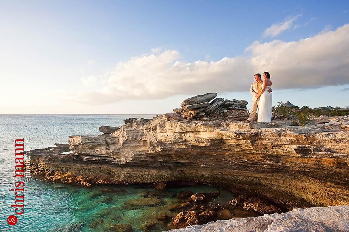 Turks & Caicos honeymoon shoot couple posing on rocks by ocean Amanyara resort Providenciales