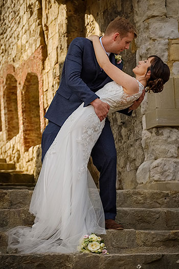 Farnham Castle Anniversary photo shoot couple embrace in Keep gateway