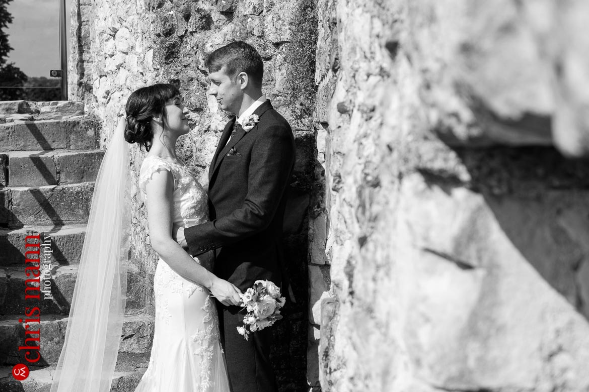 couple embrace by castle wall Farnham Castle anniversary shoot
