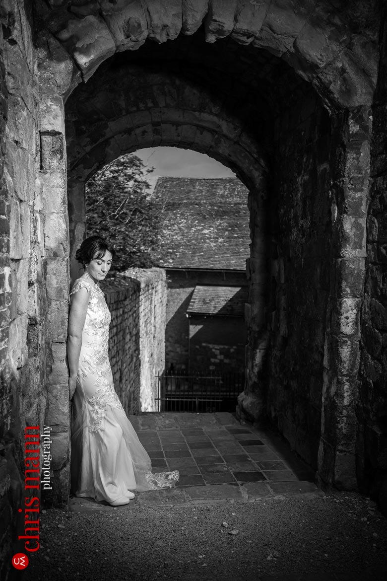 bride alone in gateway of Farnham Castle Keep anniversary shoot