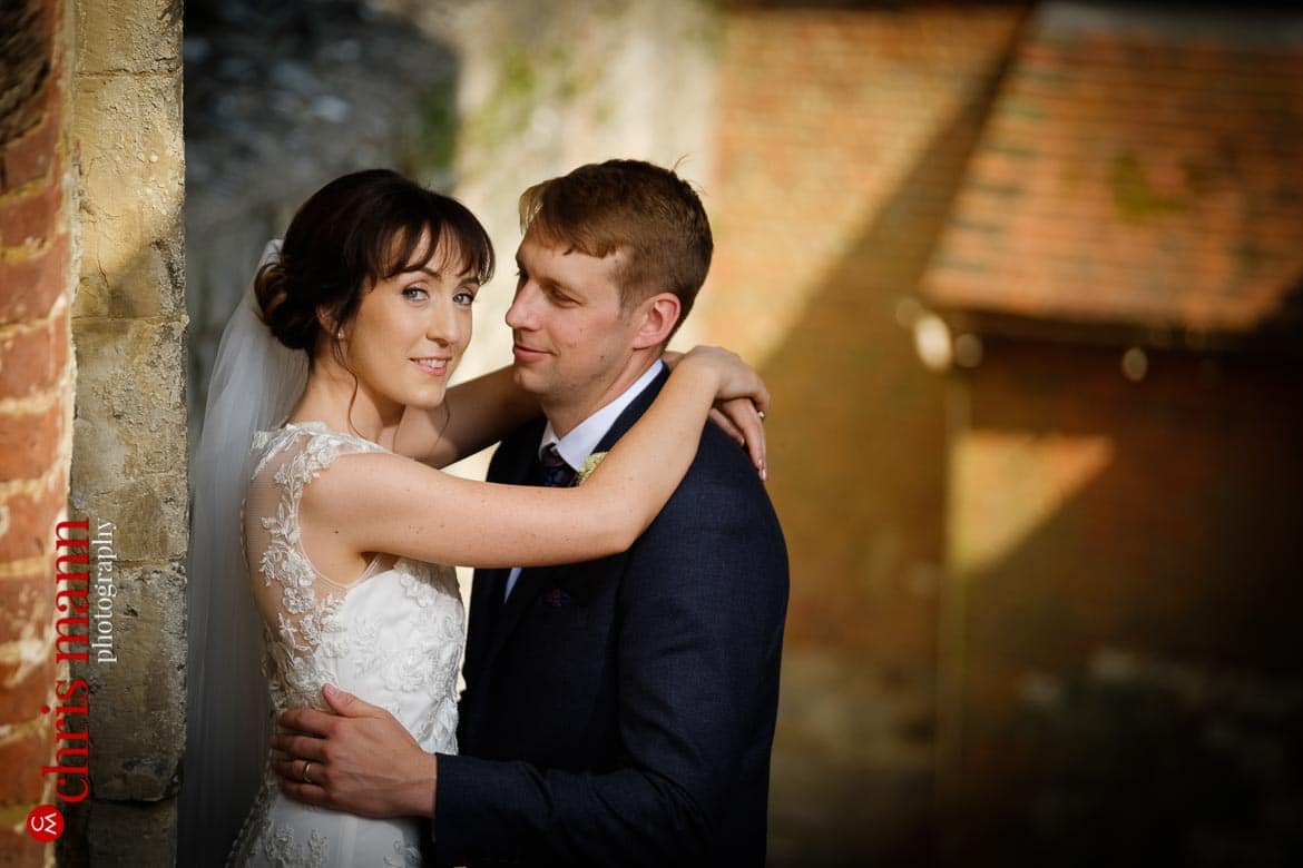 bride and groom embracing in gateway of Farnham Castle Keep - anniversary shoot