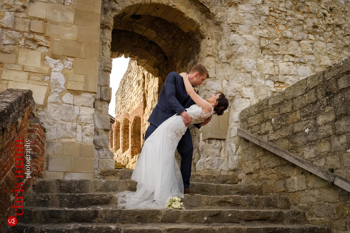 groom dips bride in castle keep gateway Farnham Castle anniversary shoot