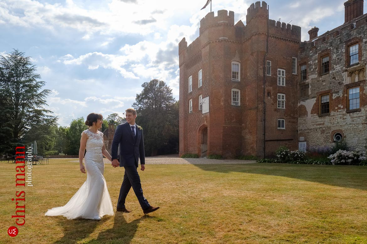 couple walking in grounds at Farnham Castle anniversary shoot