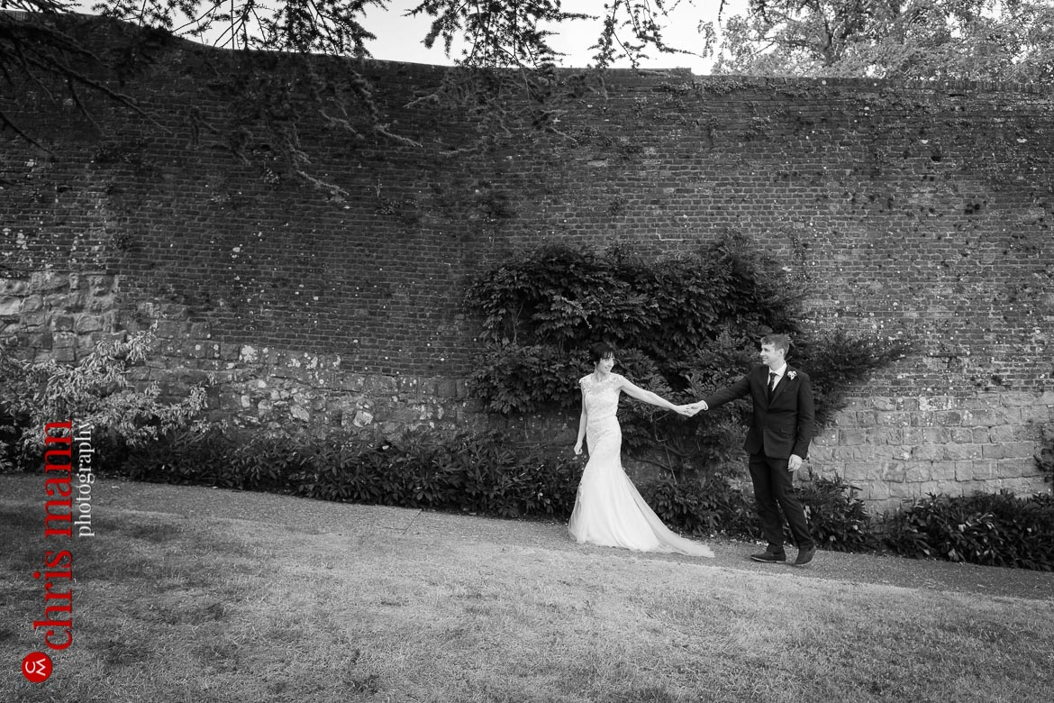 bride leads groom by the hand Farnham Castle anniversary shoot