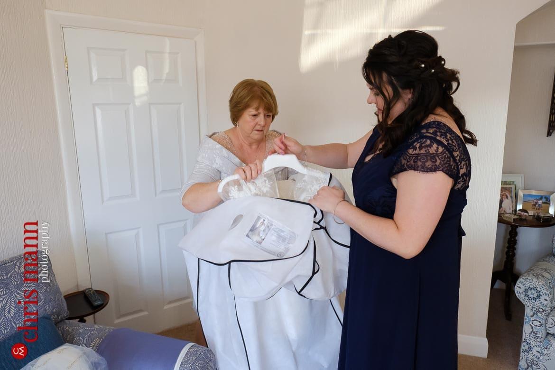 mother of bride and bridesmaid prepapre the wedding dress