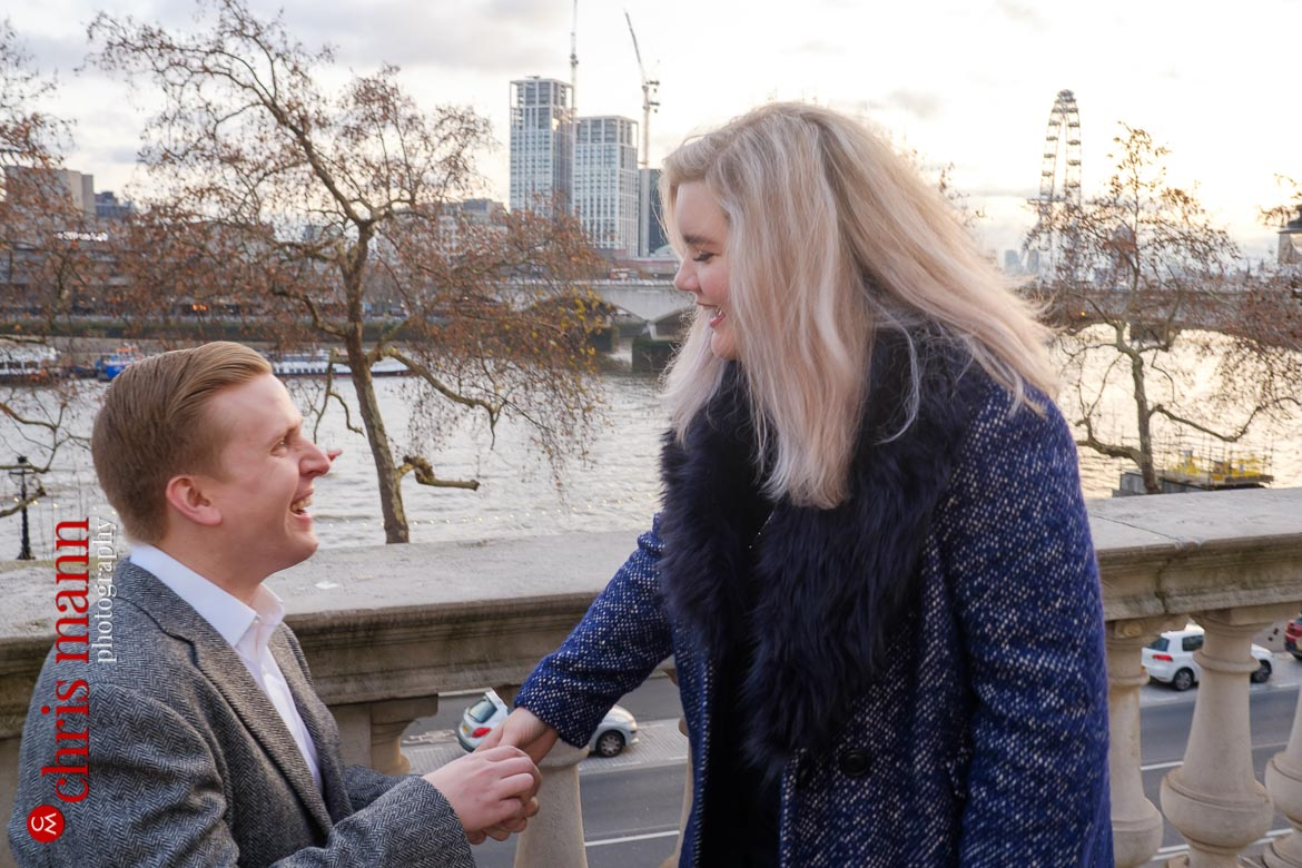 man goes down on one knee to propose to woman on the terrace at Somerset House London