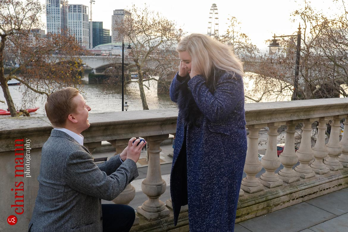 woman surprised by man offering engagement ring