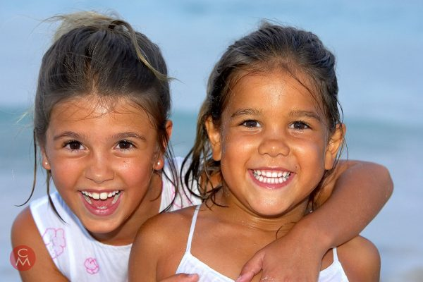 two laighing girls on the beach - portrait by Chris Mann Photography