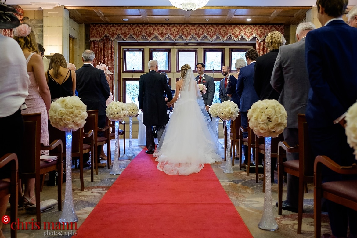 Father of the bride escorts bride into wedding ceremony in the Wordsworth Room - South Lodge Horsham wedding photography by Chris Mann