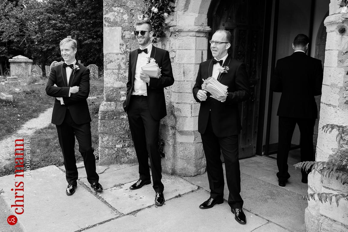 groomsmen welcome guests at Hampshire country church wedding - St Peter's Bishop Waltham