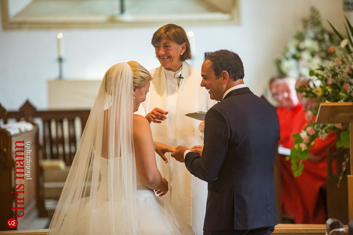 groom puts ring on bride's finger - church wedding - St Peter's Bishop Waltham