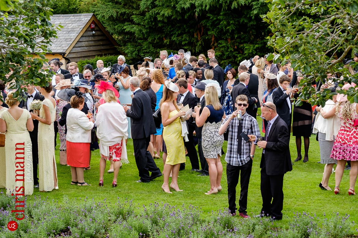 wedding guests enjoying drinks on the lawn at an English country wedding