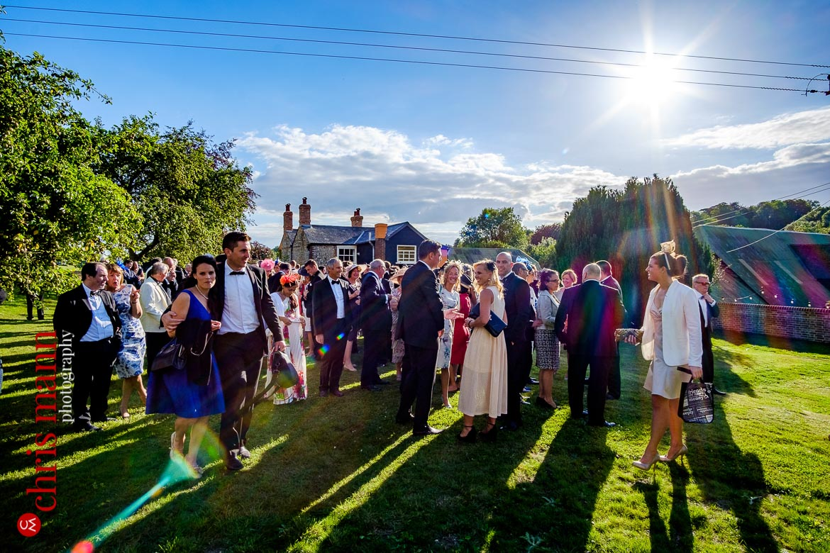 wedding guests enjoying the warm evening air as the sun dips lower