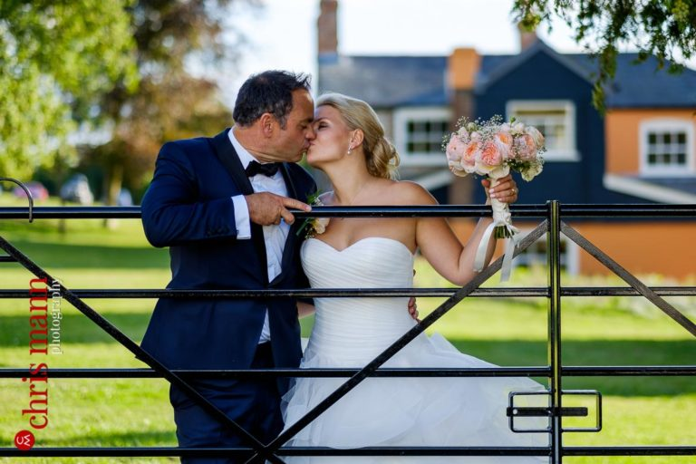 bride and groom kiss leaning over a gate