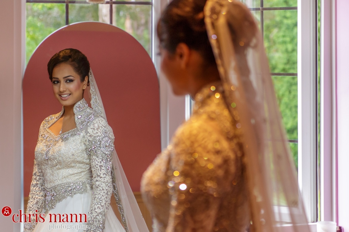 bride looks at herself in a mirror