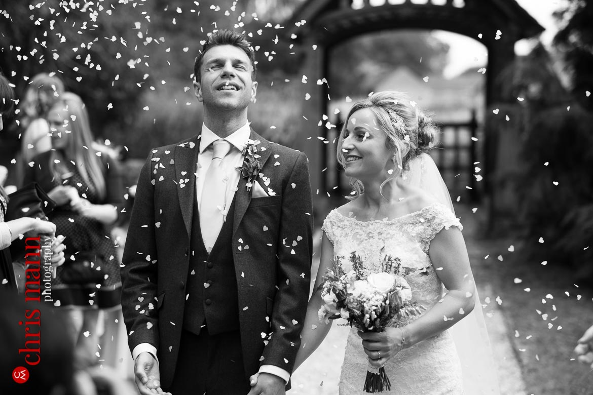 bride and groom showered in confetti at St Mary's Church Buscot Oxfordshire