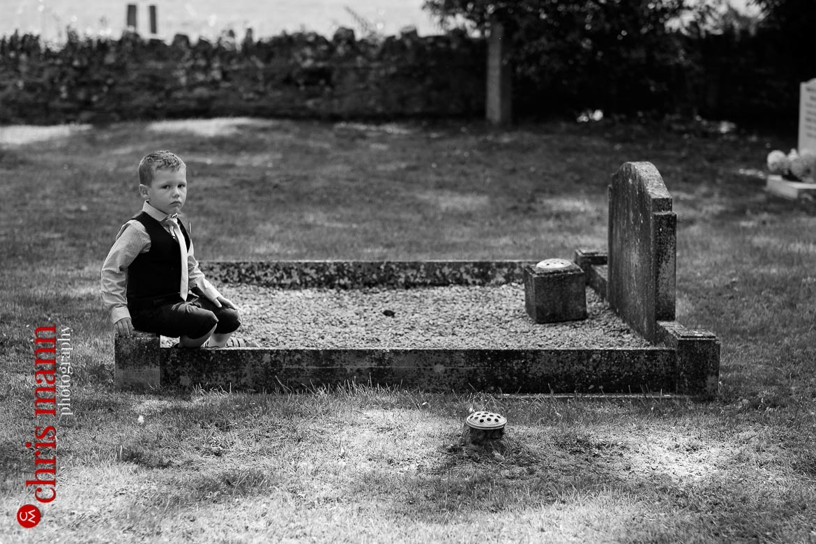 boy sits on grave at wedding in St Mary's churchyard Buscot Oxfordshire
