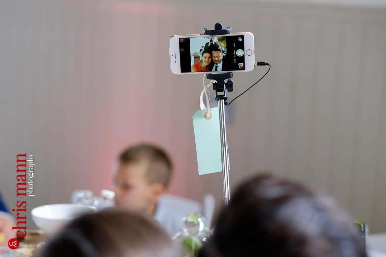 phone on selfie stick at wedding reception Oxfordshire