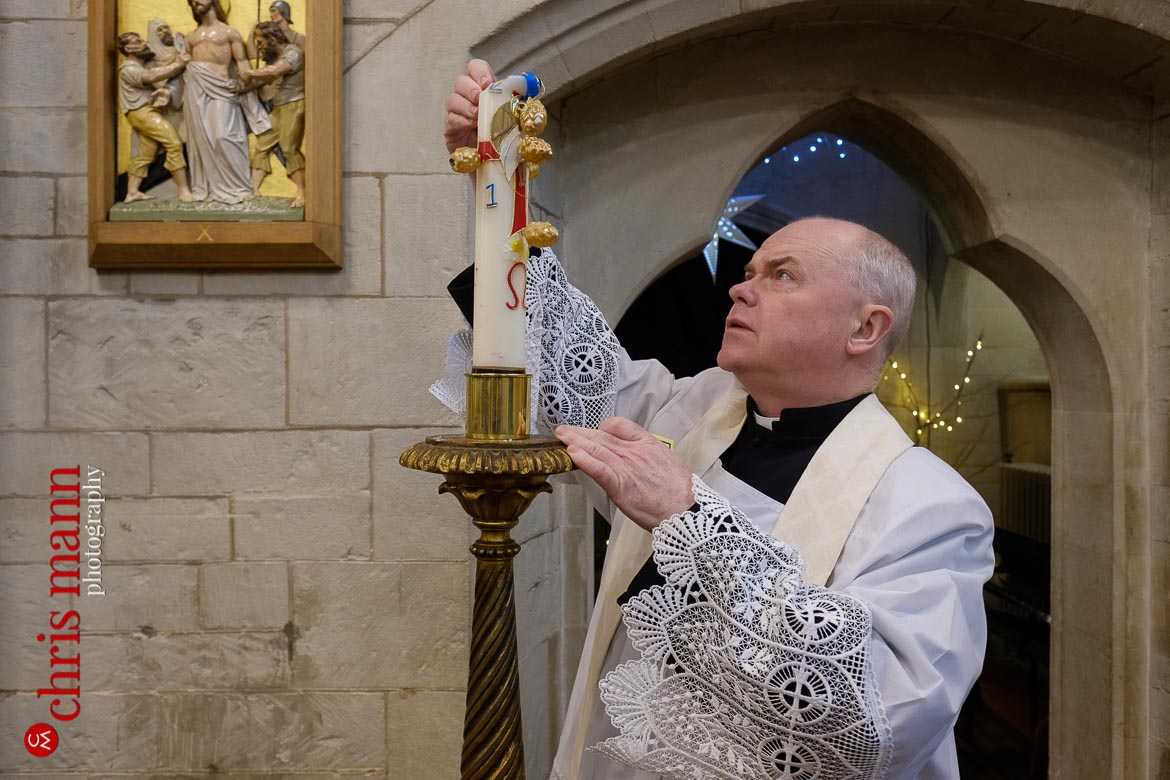 Father Sean Finnegan lights candle at Sacred Heart Church Caterham