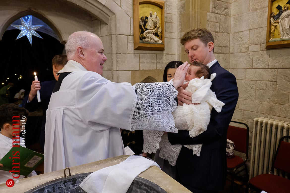 Father Sean Finnegan blesses child at baptism ceremony Sacred Heart Church Caterham